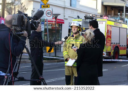 ROZELLE, AUSTRALIA - SEPTEMBER 4, 2014; Today Show Chris Urquhart and ABC news reporter are briefed by Superintendent Paul Johnstone of Fire and Rescue regarding the tragic explosion and fire. - stock photo