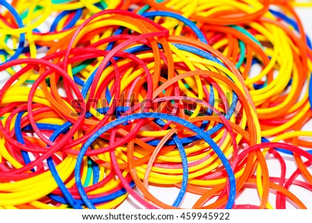 rubber bands in different colors are scattered on a white background