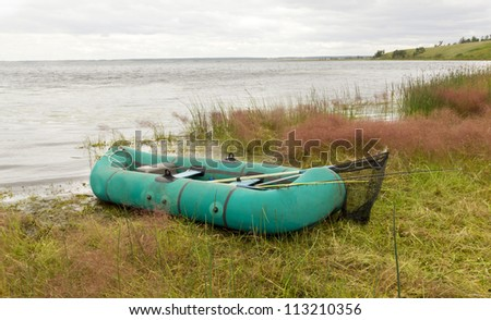 rubber boat and fishing equipment on the beach - stock photo