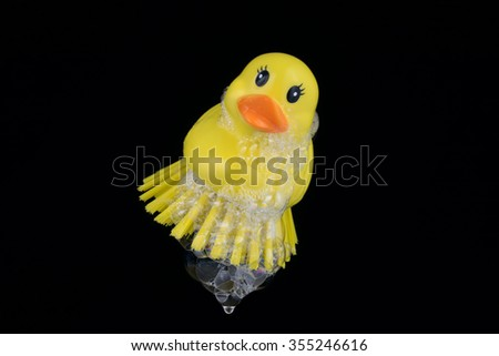 Rubber duck brush with foam isolated on black background
