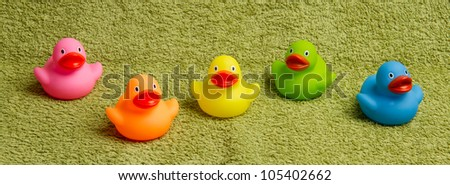 Rubber ducks isolated on a green towel - stock photo