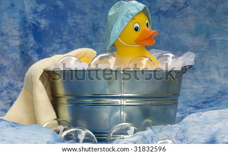Rubber Ducky taking a bath in tub and playing with bubbles.
