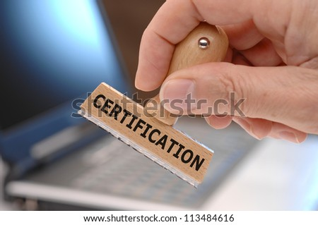 rubber stamp in hand marked with certification - stock photo