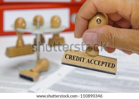 rubber stamp in hand marked with credit accepted - stock photo