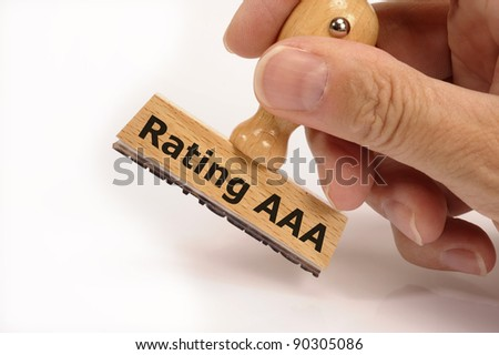 rubber stamp in hand with financial market ranking AAA