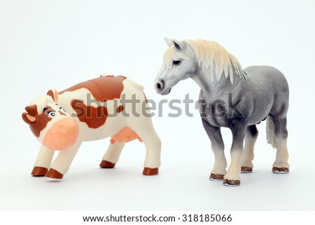 Rubber toy cow and horse on white background