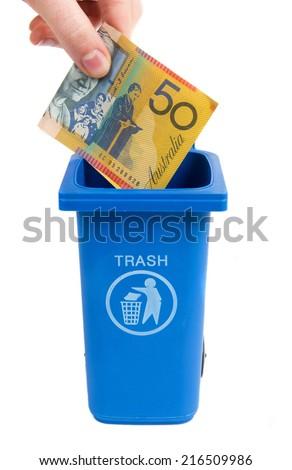 rubbish bin with australian money isolated on white - stock photo