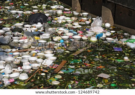 Rubbish heap are floating on canal - stock photo