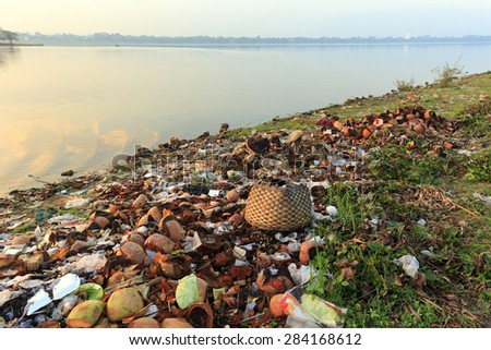 Rubbish pollution with plastic and other packaging stuffs on the bank of the Taungthaman lake near U Bein bridge in Myanmar (Burma) - stock photo