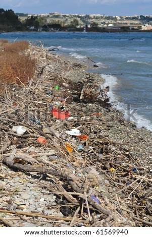 Rubbish strewn on shingle beach with sea in background. - stock photo