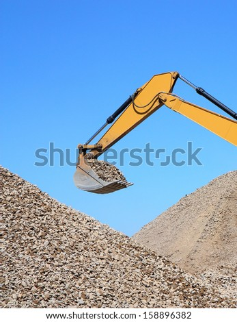 Rubble spilling out of the bucket dredge on background of blue sky