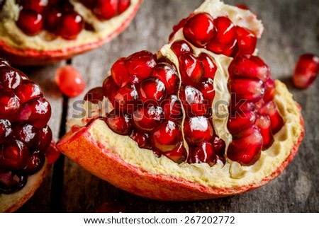 ruby juicy pomegranate grains closeup on a rustic wooden table - stock photo