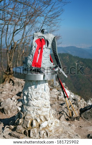 Rucksack and ski poles on the mountain summit. - stock photo