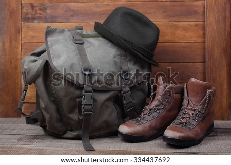 Rucksack with old boots and hat on wooden background. Traveller concept - stock photo