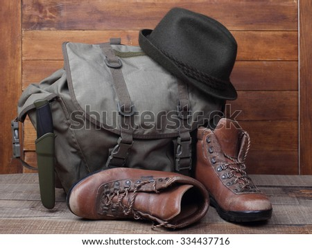 Rucksack with old boots, knife and hat on wooden background. Traveller concept - stock photo