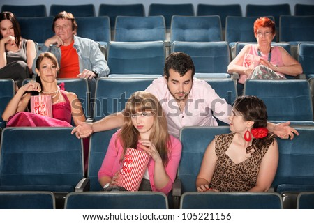 Rude bearded man talking to ladies in a theater - stock photo
