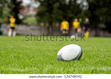Rugby ball at green grass. Photo taken at rugby training. - stock photo