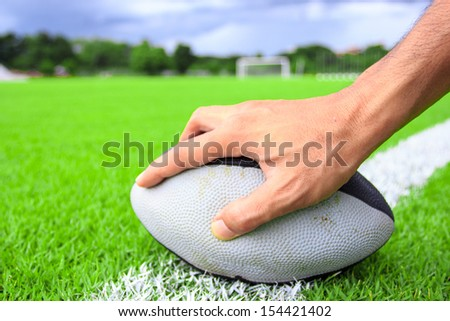 rugby ball in hand on green grass  - stock photo