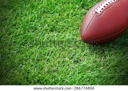 Rugby ball on green field - stock photo
