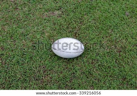 rugby ball on green grass - stock photo