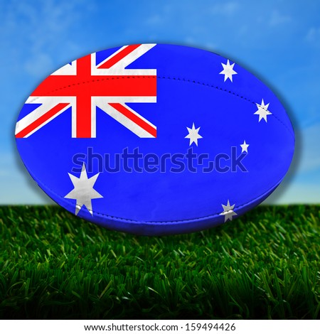 Rugby ball with Australia flag over grass - stock photo