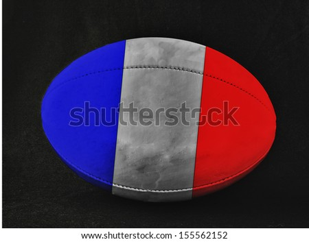 Rugby ball with France flag colors, over black background - stock photo