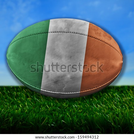 Rugby ball with Ireland flag over grass - stock photo