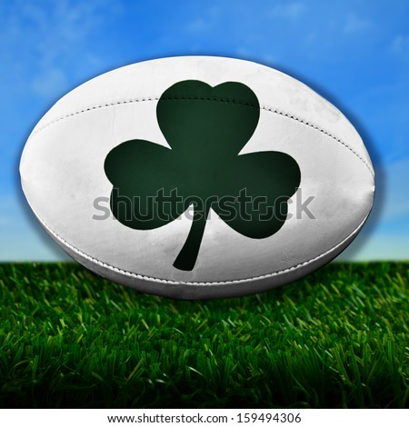 Rugby ball with Irish Shamrock over grass - stock photo