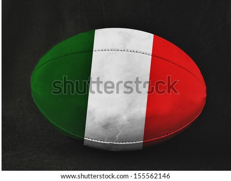 Rugby ball with Italy flag colors, over black background - stock photo