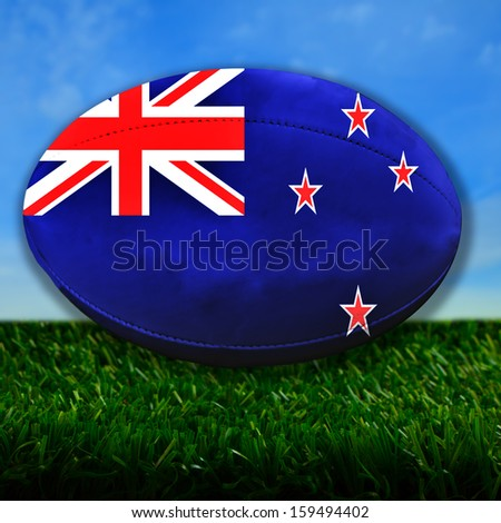 Rugby ball with New Zealand flag over grass - stock photo