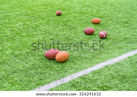 Rugby balls scattered on playing field with white line markings