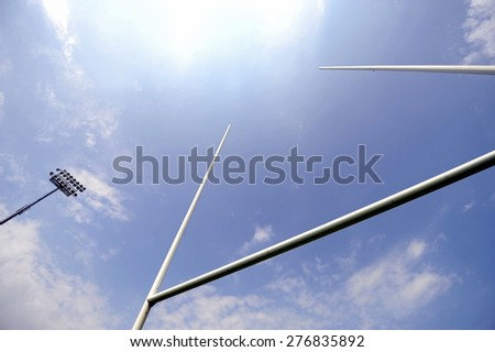 Rugby goal posts with stadium spotlights and blue sky on the background - stock photo