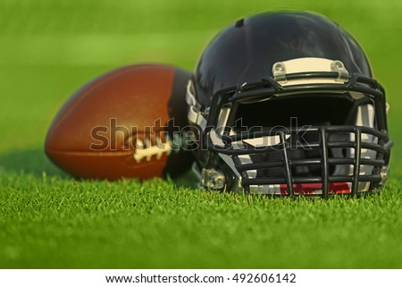Rugby helmet with ball on field