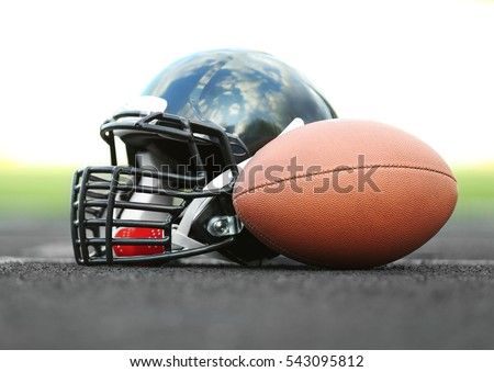 Rugby helmet with ball on ground