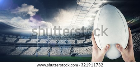 Rugby player catching a rugby ball against rugby stadium - stock photo