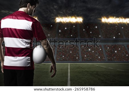 Rugby player in a red uniform on a stadium. - stock photo