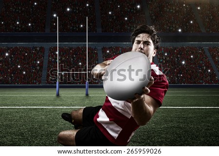 Rugby player in a red uniform scoring on a stadium. - stock photo
