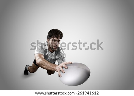 Rugby player in a white uniform scoring on a white background. - stock photo