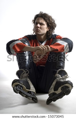 Rugby player sitting with his elbows on his knees looking angry. Vertically framed photograph - stock photo
