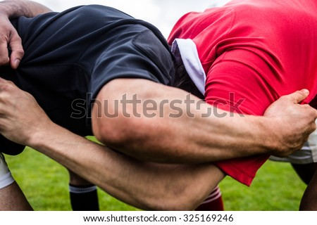 Rugby players doing a scrum at the park - stock photo