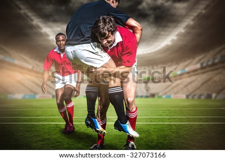 Rugby stadium against rugby players tackling during game - stock photo