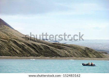 Rugged arctic landscape - blue gulf waters with expedition boat under barren mountain, melting glacier and cloudy grey sky near Longyearbyen, Spitsbergen (Svalbard), Norway, Greenland sea  - stock photo