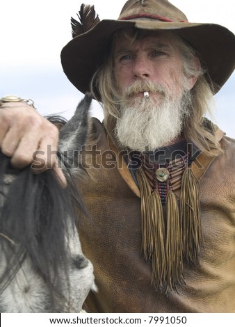 Rugged cowboy with his horse - stock photo