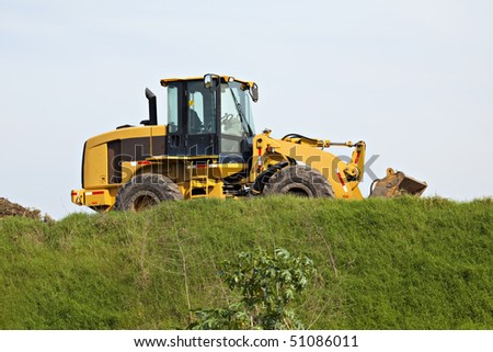 Rugged earthmoving machines sitting on grassy hill - stock photo