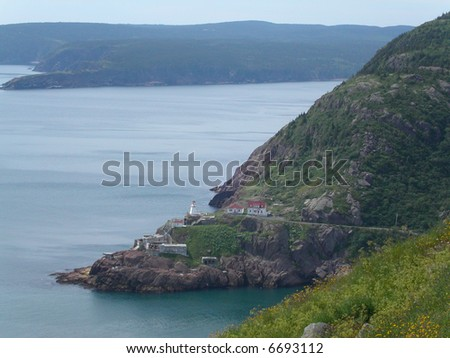 Rugged nature and lighthouse at entrance of St John's harbour.  Newfoundland.  Canada. - stock photo