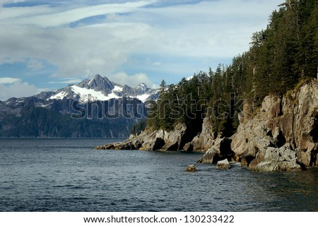 Rugged ocean coastline with snow capped mountain behind.