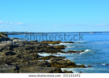 rugged shoreline of the  Casco Bay at the entrance to the harbor at Portland, Maine ; Hog Island and Portland in the far background