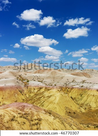 Rugged terrain in Badlands National Park, South Dakota, beneath blue sky and clouds. Vertical shot.