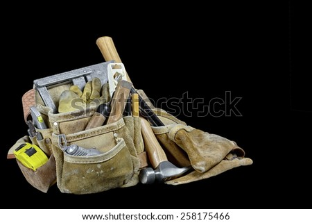 Rugged worn carpenters leather work bags and belt with construction tools and hammer isolated on black and selective focus on mitre square. - stock photo