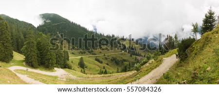 Ruhpolding panorama with winding pathway and farmhouse in Alps under clouds